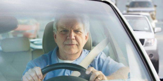 Elderly man driving car in