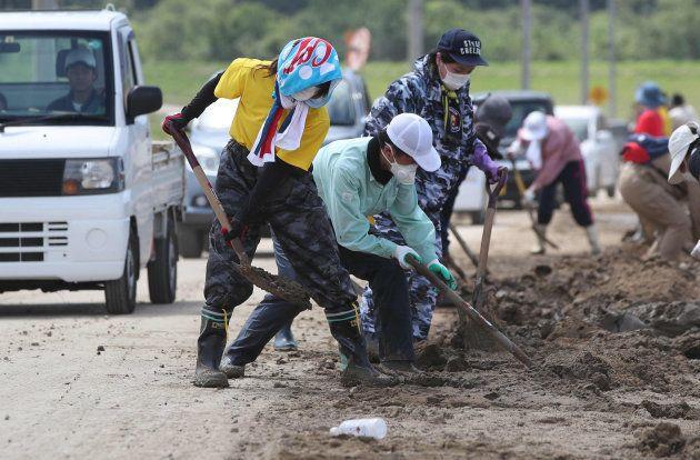 水が引いた真備町地区で、道路に残った泥をかき出す人たち=10日、岡山県倉敷市 撮影日:2018年07月10日