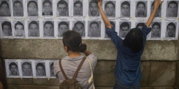 Nicaraguan demonstrators post leaflets, in protest, with the images of disappeared Mexican rural college...