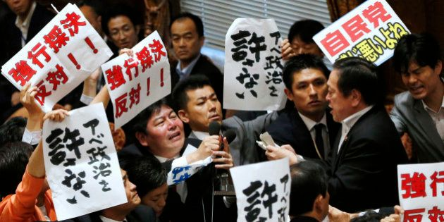 Opposition lawmakers surround Yasukazu Hamada, right, chairman of the lower house special committee on...
