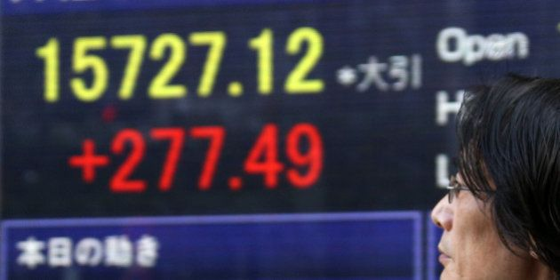 A pedestrian walks past an electronic stock board displaying the closing figure of the Nikkei 225 Stock...