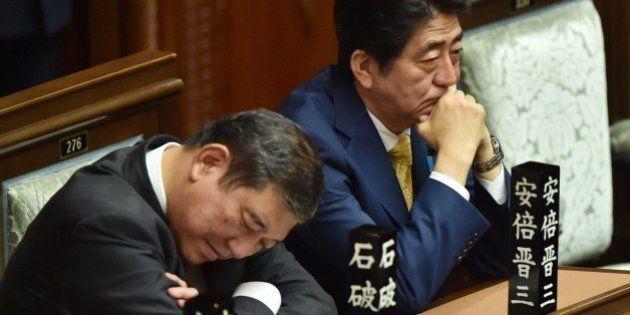 Japan's Prime Minister Shinzo Abe (R) and Regional Revitalization Minister Shigeru Ishiba (L) listen...
