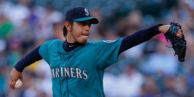 SEATTLE, WA - JULY 07: Starting pitcher Hisashi Iwakuma #18 of the Seattle Mariners pitches in the first...
