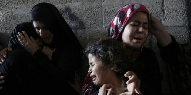 The daughters (R) of Hasan Baker, 60-years-old, grieve during his funeral in Gaza City, on July 22, 2014....