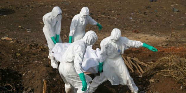 Health workers carry the body of a suspected Ebola victim for burial at a cemetery in Freetown, Sierra...