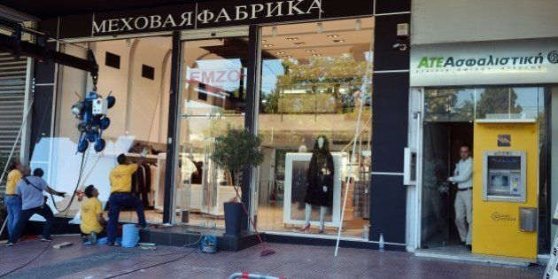 Workers replace the broken window of a fur shop in central Athens, on July 16, 2015 following last night's...