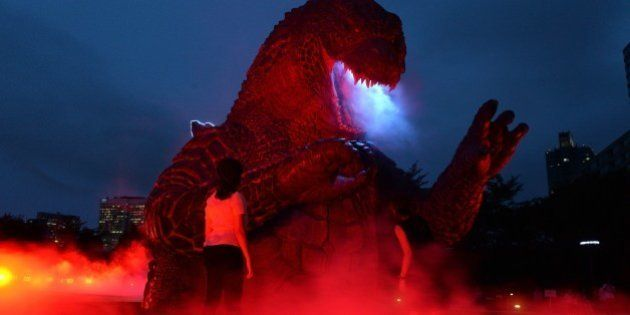 A 6.6 meter tall godzilla statue is illuminated at the Midtown park in Tokyo for the promotion of the...