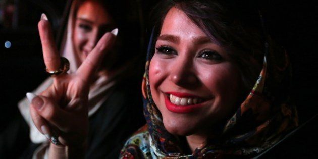 Iranian women flash the v sign for victory during celebration in northern Tehran on July 14, 2015, after...