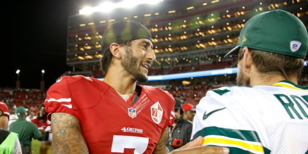 San Francisco 49ers quarterback Colin Kaepernick, left, greets Green Bay Packers quarterback Aaron Rodgers...