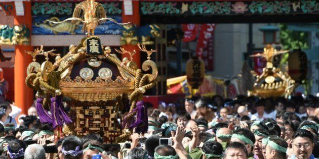 Local residents carry portable shrines into the Kanda-Myojin shrine in downtown Tokyo during the shrine's...