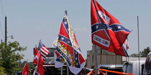 Confederate flag supporters fly their flags across the street from Durant High School, where President...