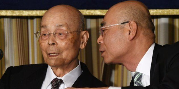 Top Japanese sushi chef Jiro Ono (L) listens to his son, Yoshikazu Ono (R), while attending a press conference...