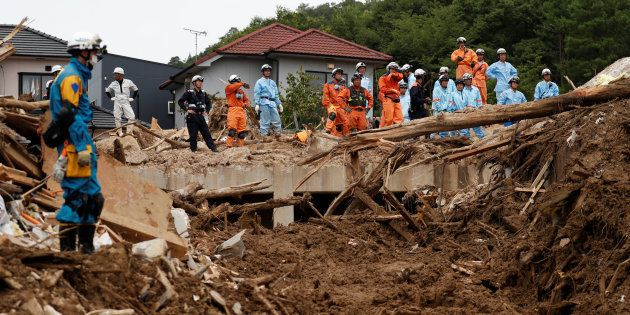Rescue workers and Japan Self-Defense Force soldiers search for missing people at a landslide site caused...
