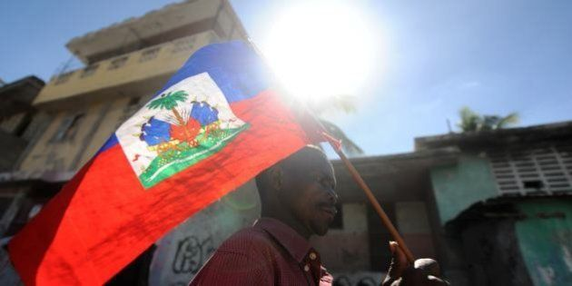 A man holds a Haitian flag as he takes part in a protest demanding that Haitian President Michel Martelly...