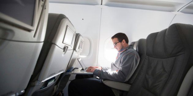 A man uses his laptop to test a new high speed inflight Internet service named Fli-Fi while on a special...