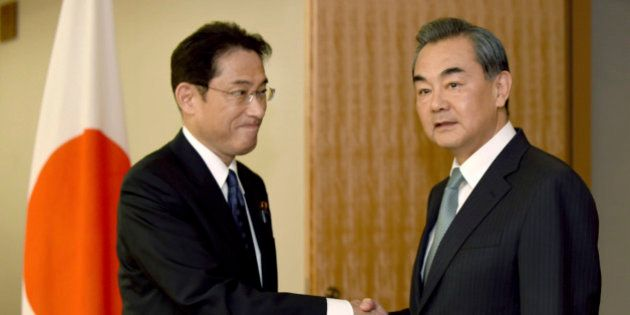 Chinese Foreign Minister Wang Yi, right, is welcomed by his Japanese counterpart Fumio Kishida prior...