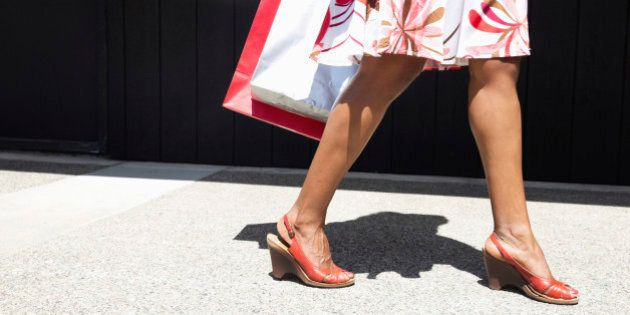 African American woman carrying shopping bags on city