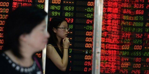 Investors check a screen displaying share prices at a security firm in Shanghai on July 6, 2015. Shanghai...