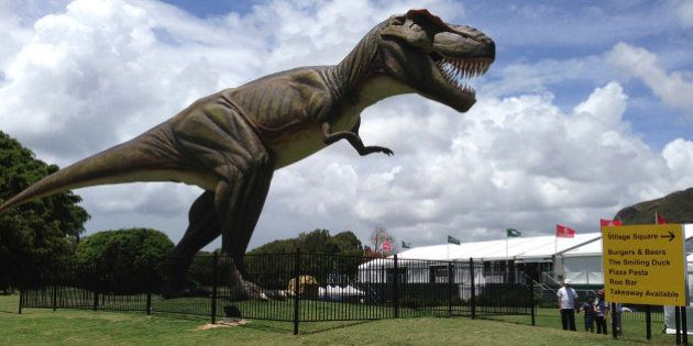 FILE - In this Dec. 11, 2012 file photo, people stand near an eight-meter (26-foot) replica of a tyrannosaurus...