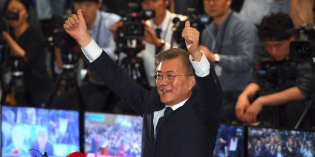 South Korean presidential candidate Moon Jae-in (C) of the Democratic Party reacts as he watches screens...
