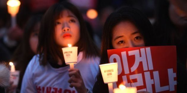 TOPSHOT - Protesters hold candles and banners calling for the resignation of South Korea's President...