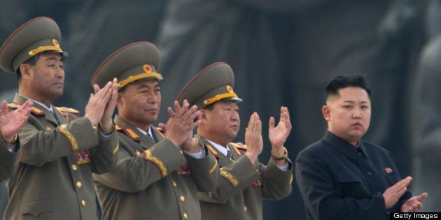 North Korean leader Kim Jong-Un (R) claps during the unveiling ceremony of two statues of former leaders...