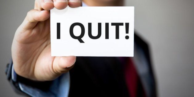 Businessman presenting 'I Quit' word on white