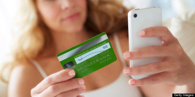 Woman using smart phone mobile device with credit card to make online