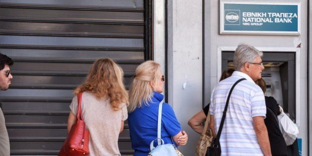 People queue at an ATM to withdraw cash in downtown Athens on July 8, 2015. Greece's government on July...