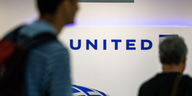 Passengers walk past signage inside the United Continental Holdings Inc. terminal at Newark Liberty International...