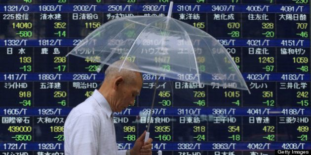 A pedestrian carrying an umbrella walks past an electronic stock board displaying falling share prices...