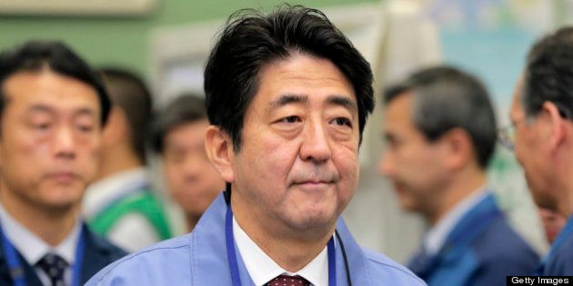 Shinzo Abe, Japan's prime minister, walks through the emergency operations center at Tokyo Electric Power...
