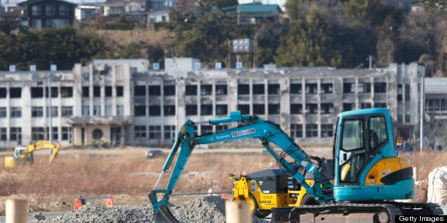 An excavator operates on a construction site as an abandoned elementary school stands in the background...