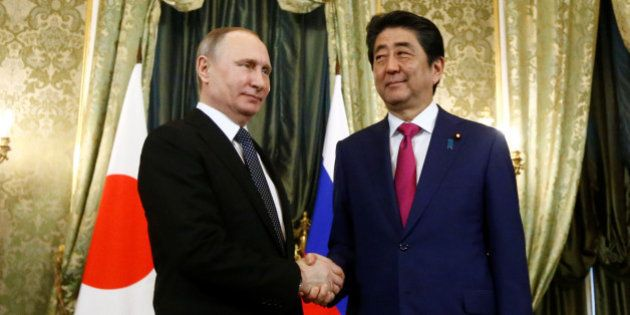 Russian President Vladimir Putin shakes hands with Japanese Prime Minister Shinzo Abe during a meeting...