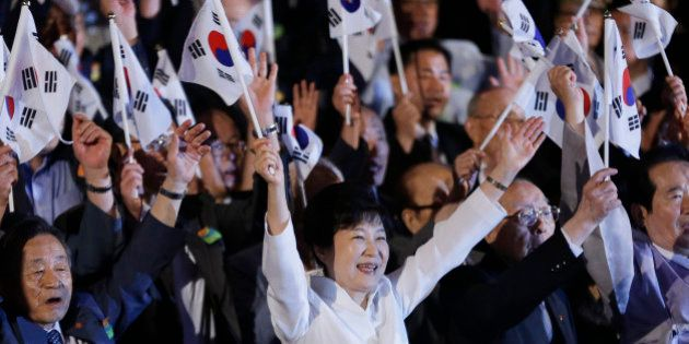 South Korean President Park Geun-hye, bottom center, gives three cheers for her country during a ceremony...