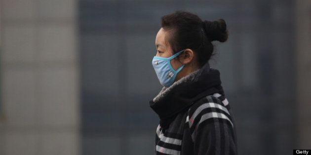 A woman wears a mask as she walks on a street in Beijing, China, on Friday, March 15, 2013. China's new...