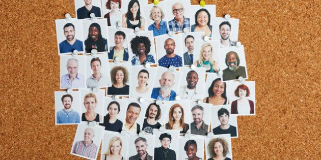 Grid of multi-ethnic portraits stuck to cork board representing community and our social and professional
