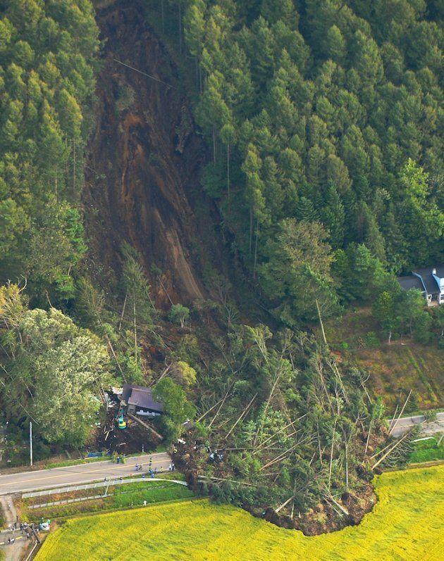 地震で発生した大規模な土砂崩れの現場。左下は倒壊した家屋周辺で行われている捜索=北海道厚真町上空