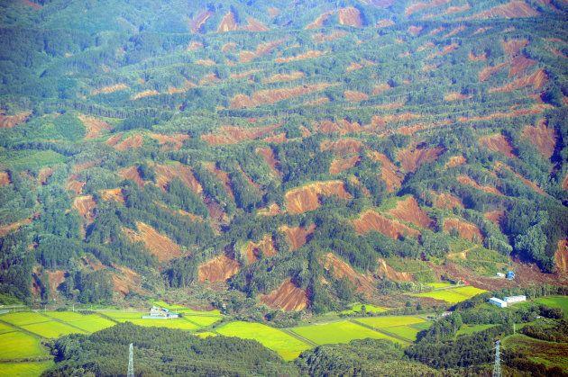 広範囲に発生した地滑りでむき出しになった山肌=北海道厚真町上空