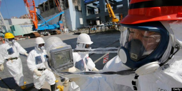 A radiation monitor reads 114.00 microsieverts per hour as members of the media and Tokyo Electric Power...