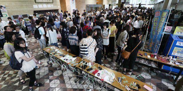 携帯電話の充電を待ち、市役所ロビーを埋め尽くす人たち=9月6日午後、札幌市中央区