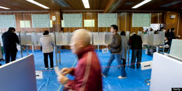 Voters cast their ballots at a polling station in Tokyo, Japan, on Sunday, Dec. 16, 2012. Japanese voters...
