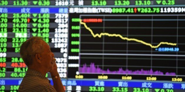 A man speaks in front of monitors showing market movements at the Taiwan Stock Exchange in Taipei on...