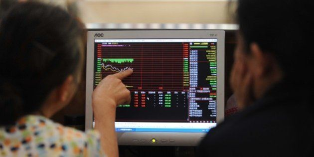 Investors talk to each other as they check stock prices at a securities firm in Wuhan, in central China's...