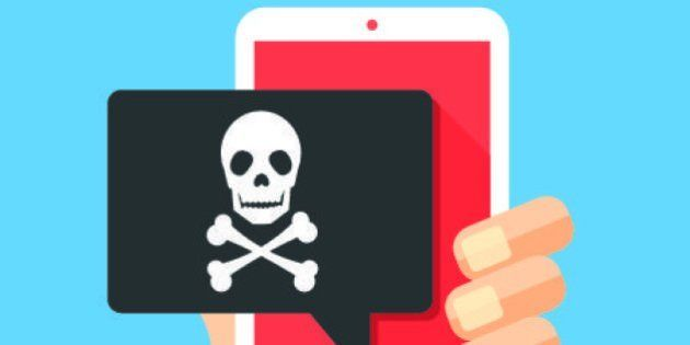 Hand holding smartphone with speech bubble and skull and bones on screen. Skull icon. Threats, mobile...