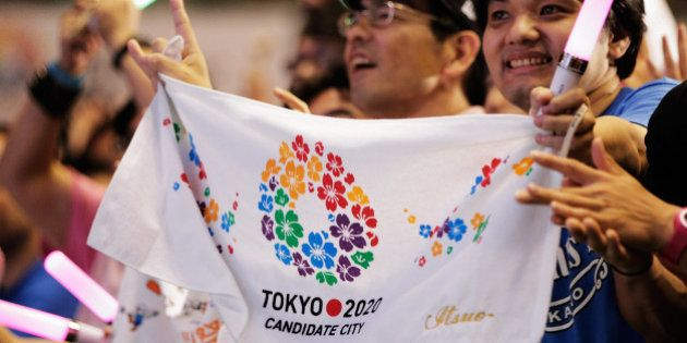 TOKYO, JAPAN - SEPTEMBER 08: Residents of Olympic bid city Tokyo celebrate while holding Tokyo signs...