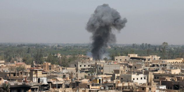 A photo taken on August 13, 2013 shows smoke billowing from buildings in Syria's eastern town of Deir...