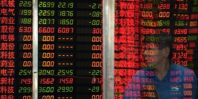 An investor is reflected in a glass window in front of a screen displaying share prices at a security...