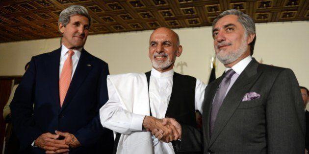 US Secretary of State John Kerry (L) looks at Afghan presidential candidates Ashraf Ghani (C) and Abdullah...