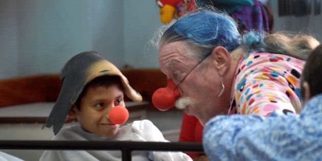 Dr. Hunter Patch Adams talks with a boy on a hospital bed at a public pediatric hospital in Panama City,...